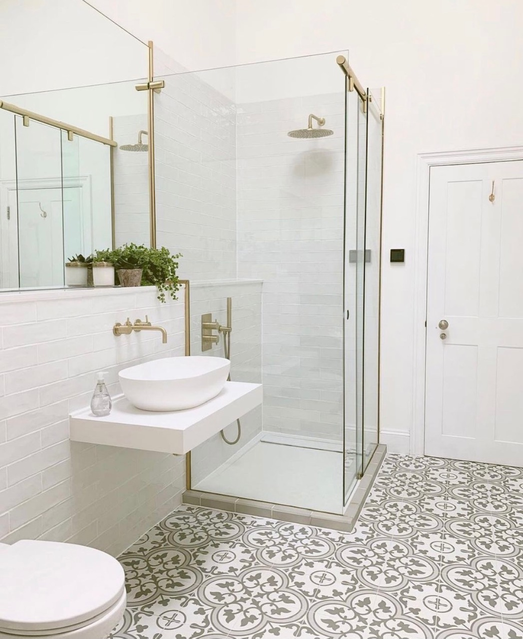 white bathroom with gold accents. Sink and shower